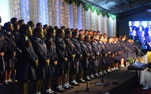 A school choir sings an invocation during the event